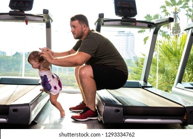 Young father and little cute daughter in the gym on a treadmill.