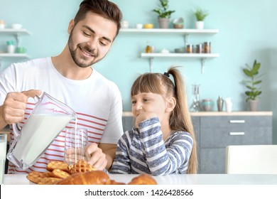 Young father with little daughter drinking tasty milk in kitchen at home
