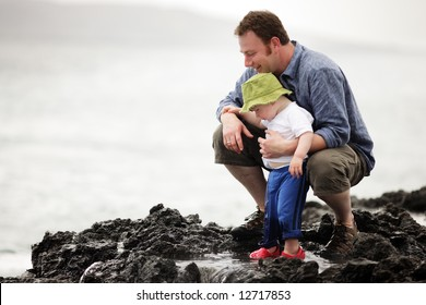 Young father with little son outdoors at ocean
