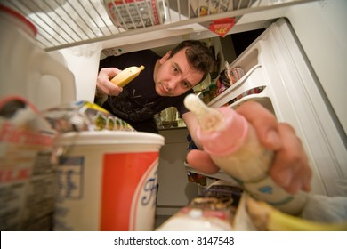 young father look into refrigerator and take bottle of milk