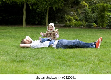 Young father lying in grass with a baby sitting on his belly