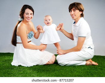 young father and mother with baby in white