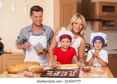 Young father and mother making cake together. boy and girl help baking at kitchen