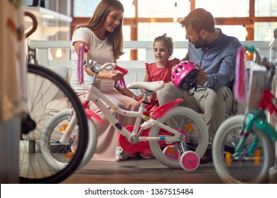 Young father and mother shopping new bicycle for happy little child in bike shop