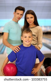 Young father and mother with son in bowling club; focus on boy; shallow depth of field