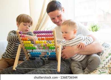 A young father on maternity leave home is teaching his eldest child. The boy learns to count on color beautiful accounts. The younger son sits in the arms of the parent