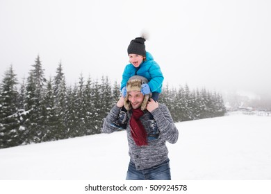 Young father outside giving his son piggyback. Having fun with his son, playing in the snow. Foggy white winter nature.