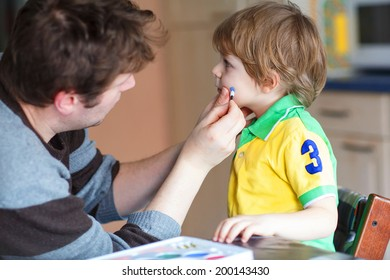 Young father painting brazilian flag on face of little boy for football or soccer game. Selective focus