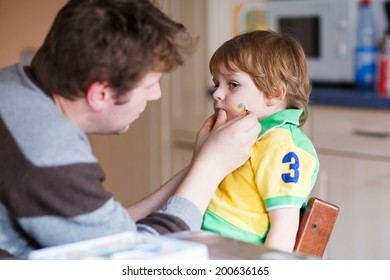 Young father painting brazilian flag on face of little boy . Selective focus
