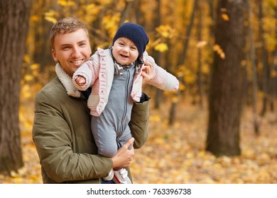 young father play with a little daughter in autumn park. Dad holding baby girl in hands. Happy family