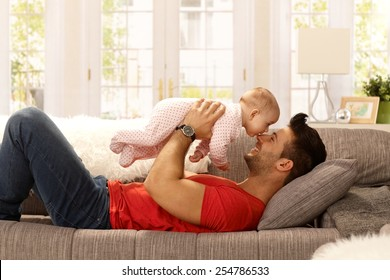 Young father playing with baby daughter as lying on sofa at home, smiling happy having fun. Side view.