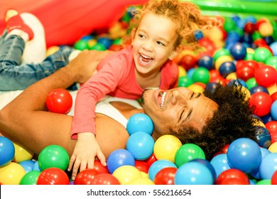 Young father playing with his daughter inside ball pit swimming pool - Happy people having fun in children playground indoor - Family and love concept - Focus on man face - Warm vivid filter