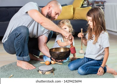 Young father playing on brass Tibetan singing bowl and teaching two beautiful daughters how to do that.Sound therapy and meditation concept