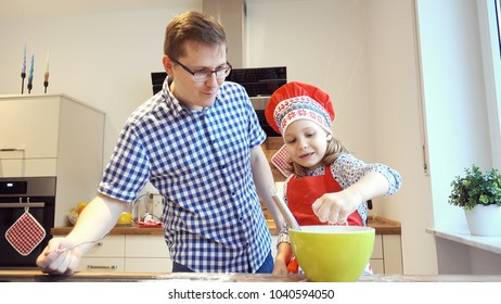 Young father with pretty little daughter backing cookies and having fun in modern kitchen