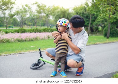 Young father put helmet on Cute little Asian 2 year old toddler baby boy child, Dad and son having fun with balance bike (run bike) on nature at park, Dad tech son to ride bike, father's day concept