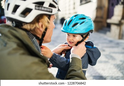 A young father putting on a helmet on his toddler son's head outdoors in city.