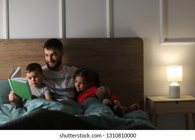 Young father reading book for his children in bed