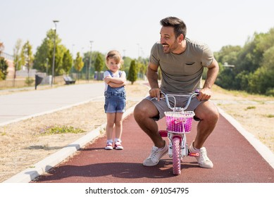 Young father riding bike while his daughter staring at him with crossed arms