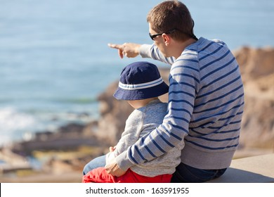 young father showing something to his son at the lookout