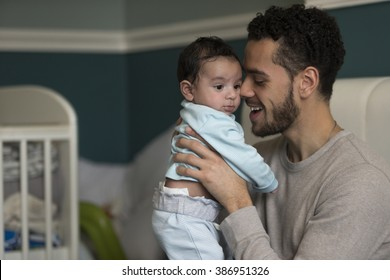 Young father sitting on his bed, holding his baby son. He has his nose pressed to his son's cheek.