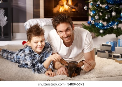Young father and son lying on floor, playing with puppy received for christmas.