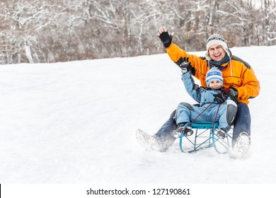 Young father and son sledding at winter time