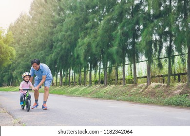 Young father spend time with Cute little Asian 2 years old toddler boy child, Dad and son having fun with balance bike (run bike) on nature, Dad tech son to ride bike, father's day concept - film look