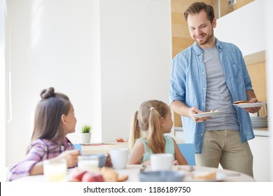 Young father taking care of his two little daughters and bringing them homemade pastry for tea
