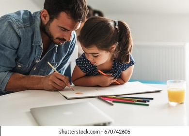 Young father  teach his daughter to draw.They sitting at the table  in living room.Natural light ambient.
