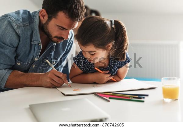 El padre joven enseña a su hija a dibujar. Se sientan en la mesa en el salón. Ambiente de luz natural.