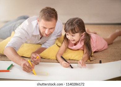 Young father teaching daughter to paint a picture on the floor. Happy time together. Setup studio shooting.