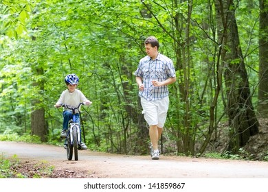 Young father teaching his son to ride a bike
