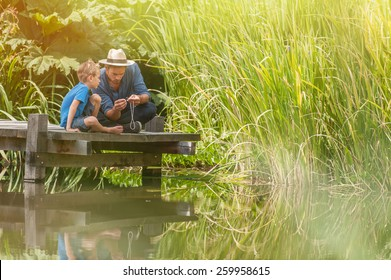 young father teaching his son to make a fishing rod, they are sitting on a wood pontoon on a river