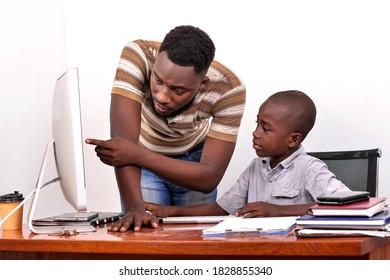 a young father in a T-shirt standing in office guiding his son to work using a computer.