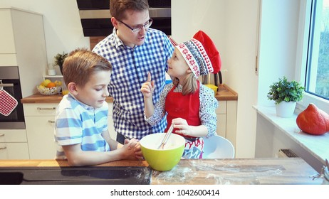 Young father with two happy children backing cookies and having fun in modern kitchen