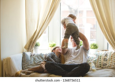 Young father with two sons playing on a cozy sofa. Dad is on maternity leave. Home entertainment with children