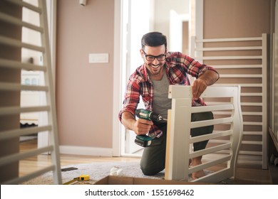 Young father using electric screwdriver to assemble the crib for new family member