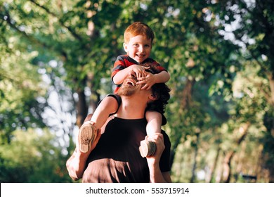 Young father walking with his young son in the park in the summer and keeps it on his shoulders