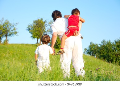 Young father in white with boys on beautiful meadow