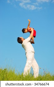 Young father in white with child on beautiful meadow