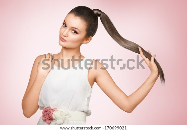 Young femail with healthy shining brown hairs put in pony tail.