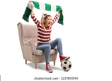 Young femal soccer fan cheering with a scarf and sitting in an armchair isolated on white background