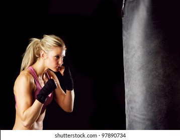 Young female in 20s boxing on a punching bag.
