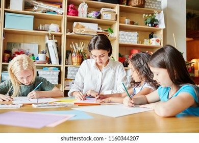 Young female and adorable girls sitting at table and drawing during art class in school