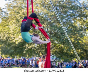 Young female aerial acrobatic dancer on a red ribbon