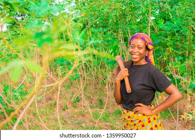 young female african farmer carrying a hoe on a farm smiling