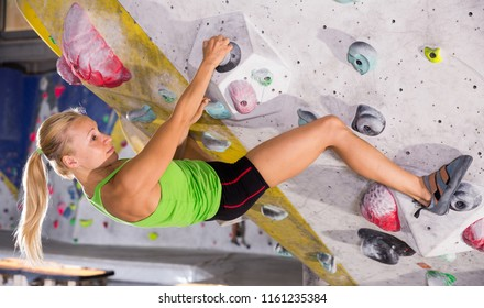 Young female alpinist practicing indoor rock-climbing on artificial boulder without safety belts
