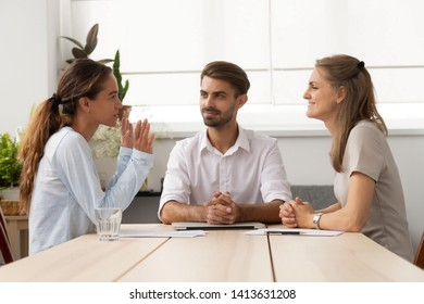 Young female applicant talking to diverse hr managers sitting at office desk. Male executive manager and colleague interviewing listening answer young girl candidate. Successful hiring process concept