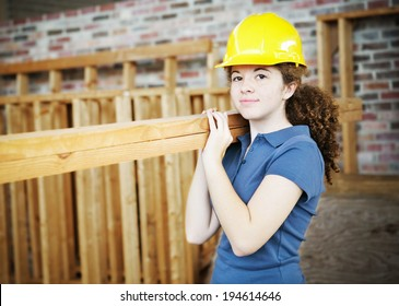Young female apprentice carrying boards on a construction site.