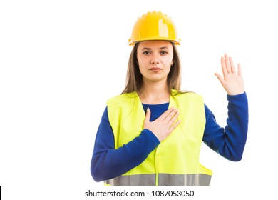 Young female architect or engineer making vow gesture with raised hand as professional sewar promise isolated on white background